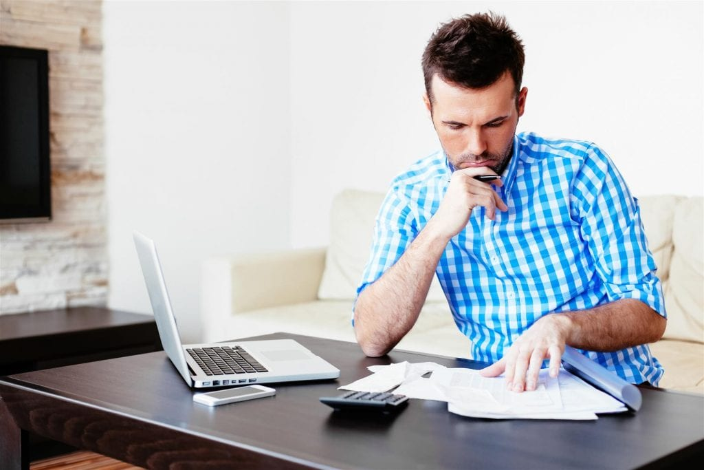 Guy With Laptop And Financial Documents