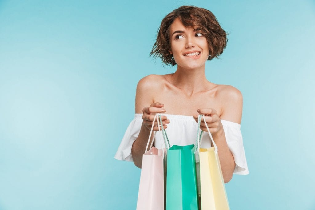 Smiling-pensive-woman-holding-shopping-bags