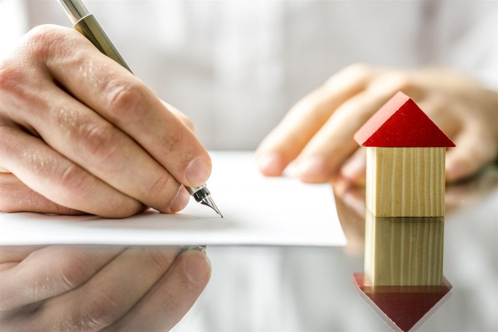 Man Signing A Mortgage Or Insurance Contract