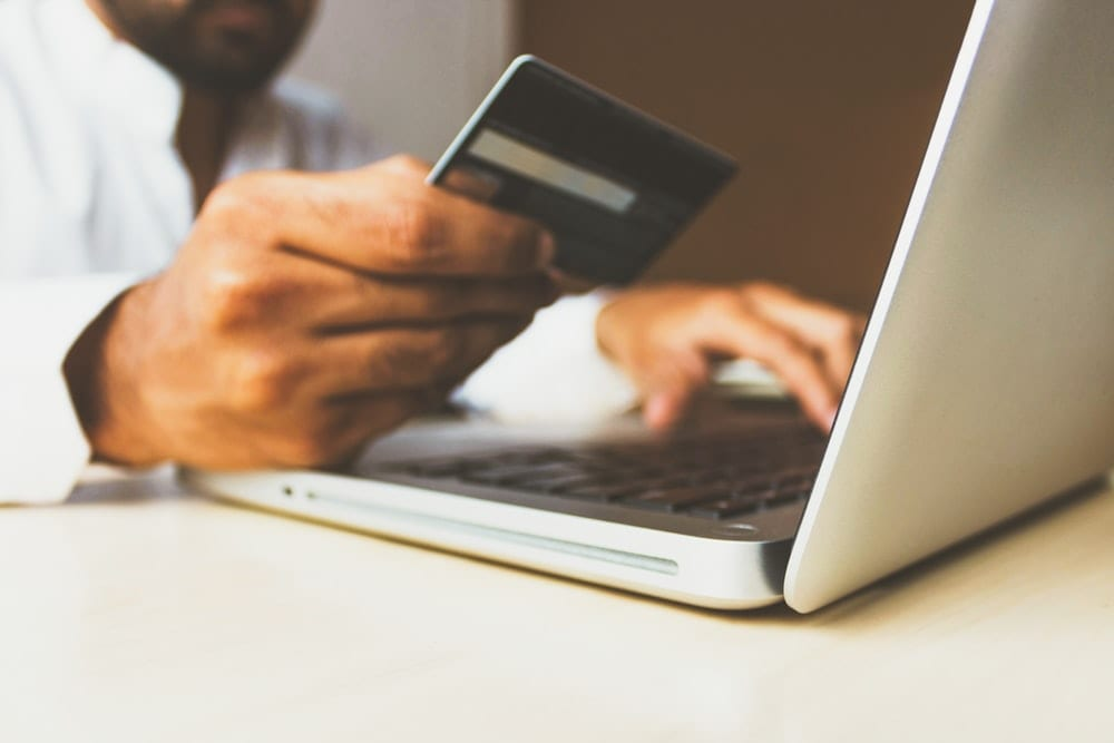 Man's Hands Holding A Credit Card And Using Laptop For Online Shopping