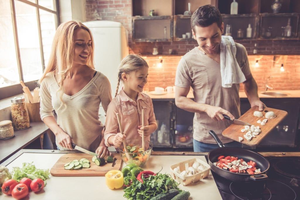 smiling family cooking in kitchen at home