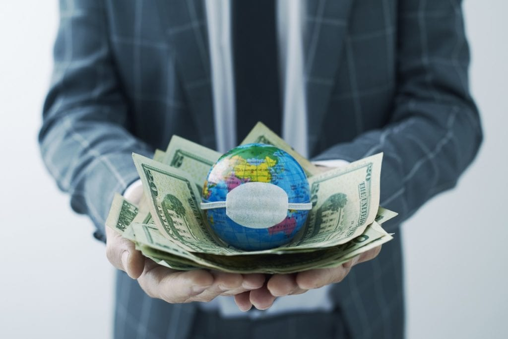 businessman holding a world globe with a protective mask on top of a handful of dollar bills