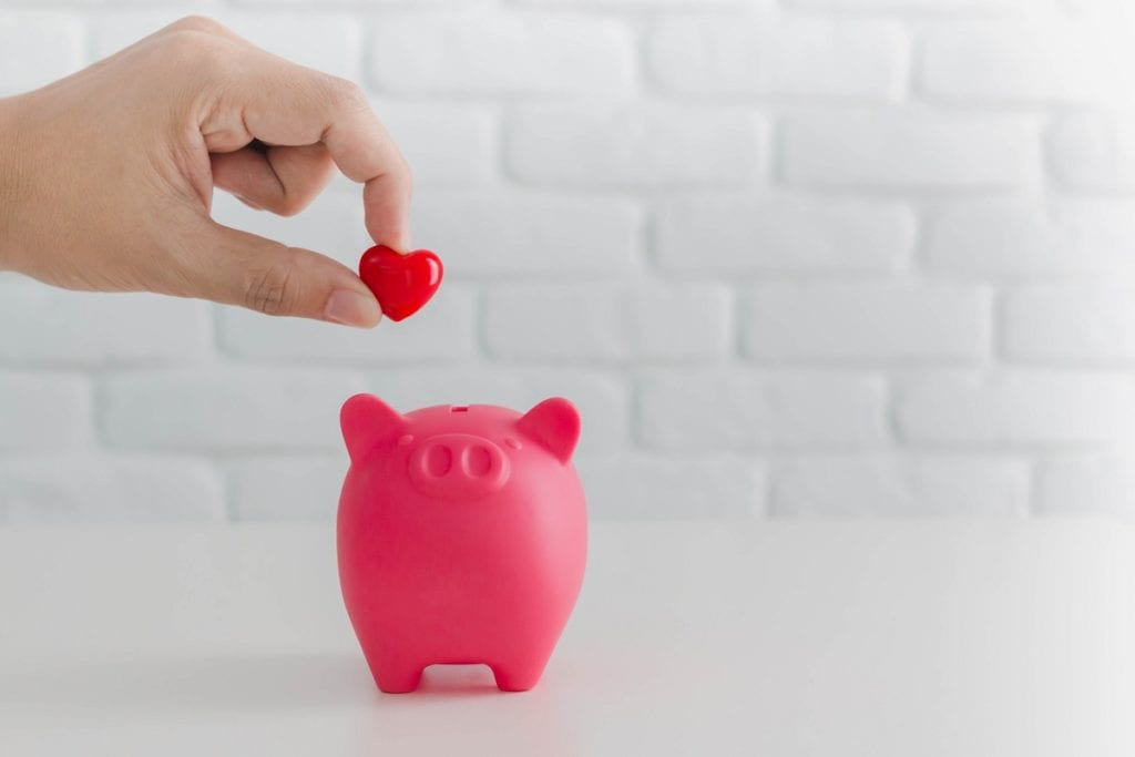 Man's hand putting red heart in to piggy bank