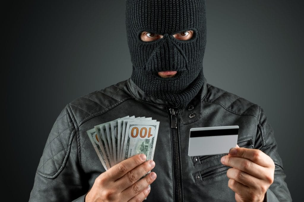 Robber in a balaclava holds a credit card in his hands