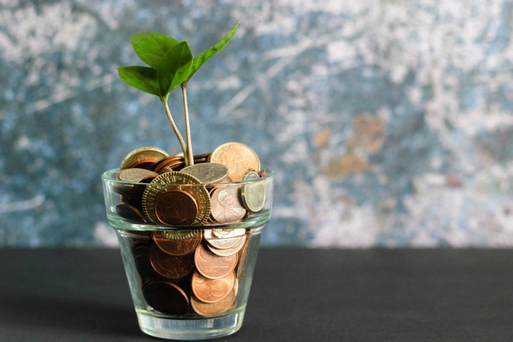 Coin in glass jar and Plant growing with savings money