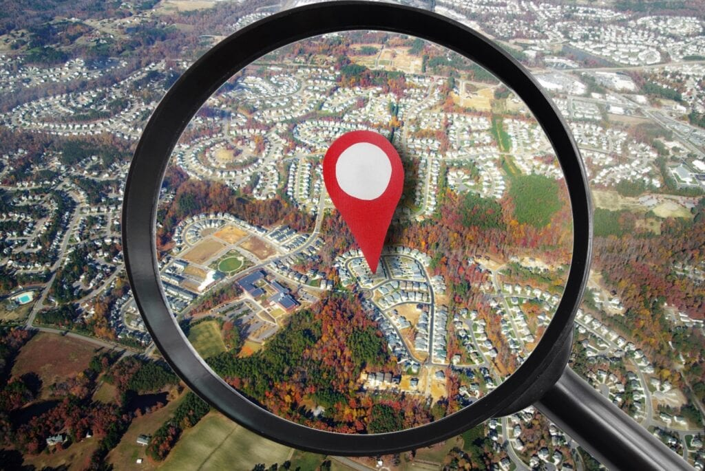 magnifying glass and red locator symbol on house from the air