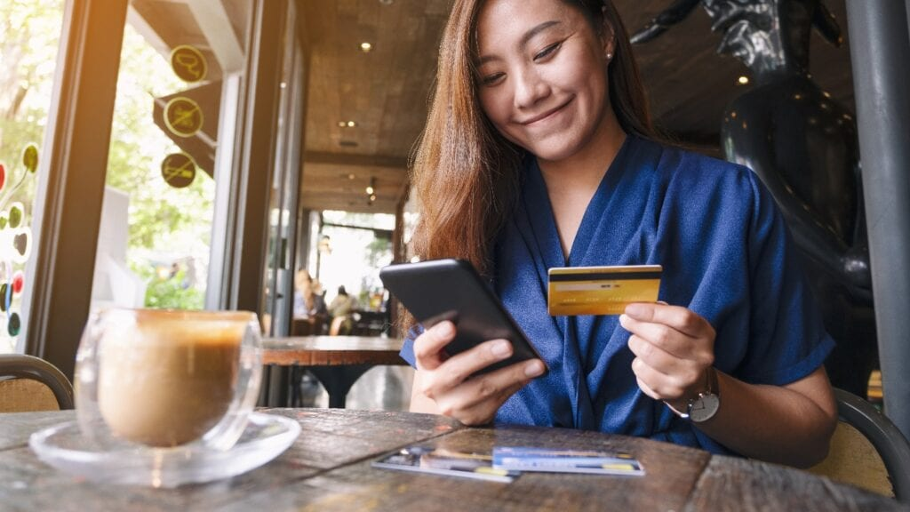 asian woman using credit card for purchasing and shopping online on mobile phone