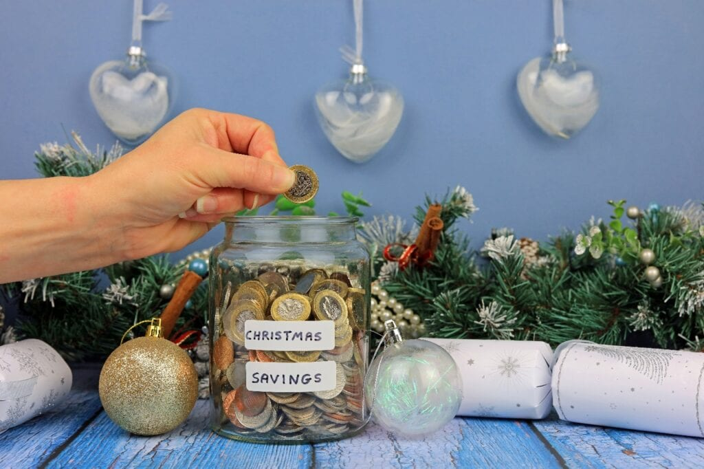 Hand put coin in glass jar, saving money for Christmas