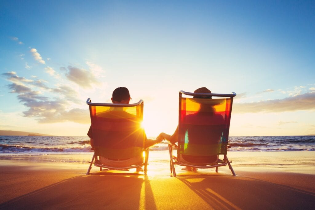 Happy Mature Retired Couple Enjoying Beautiful Sunset at the Beach