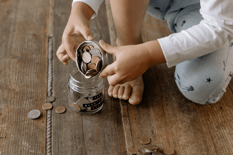 Child hand putting coin into glass