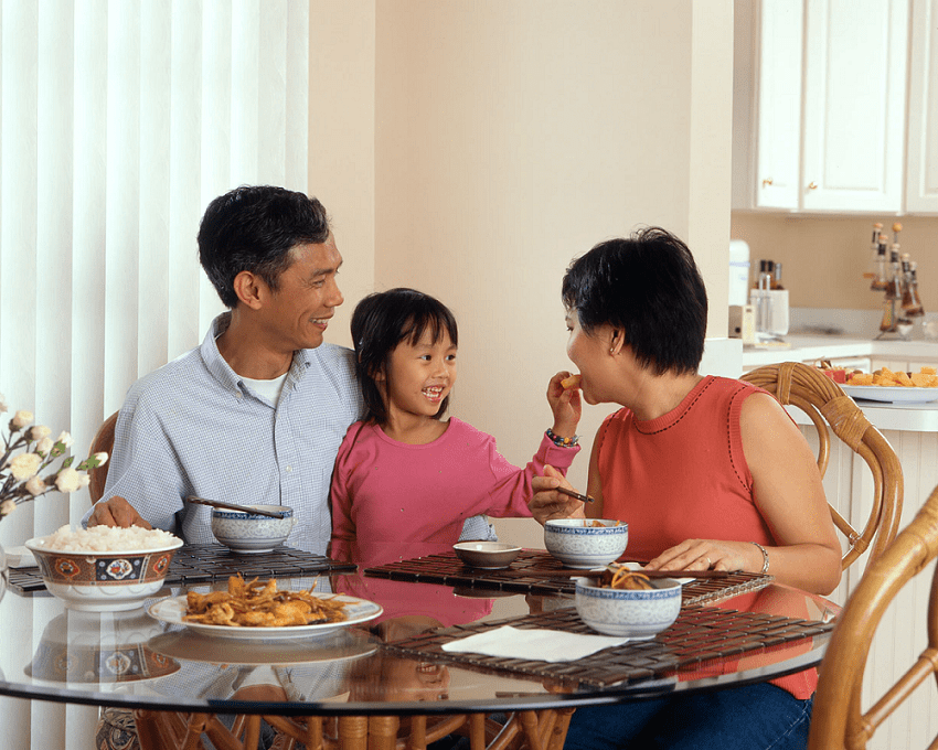 An Asian family seated around a table and eating
