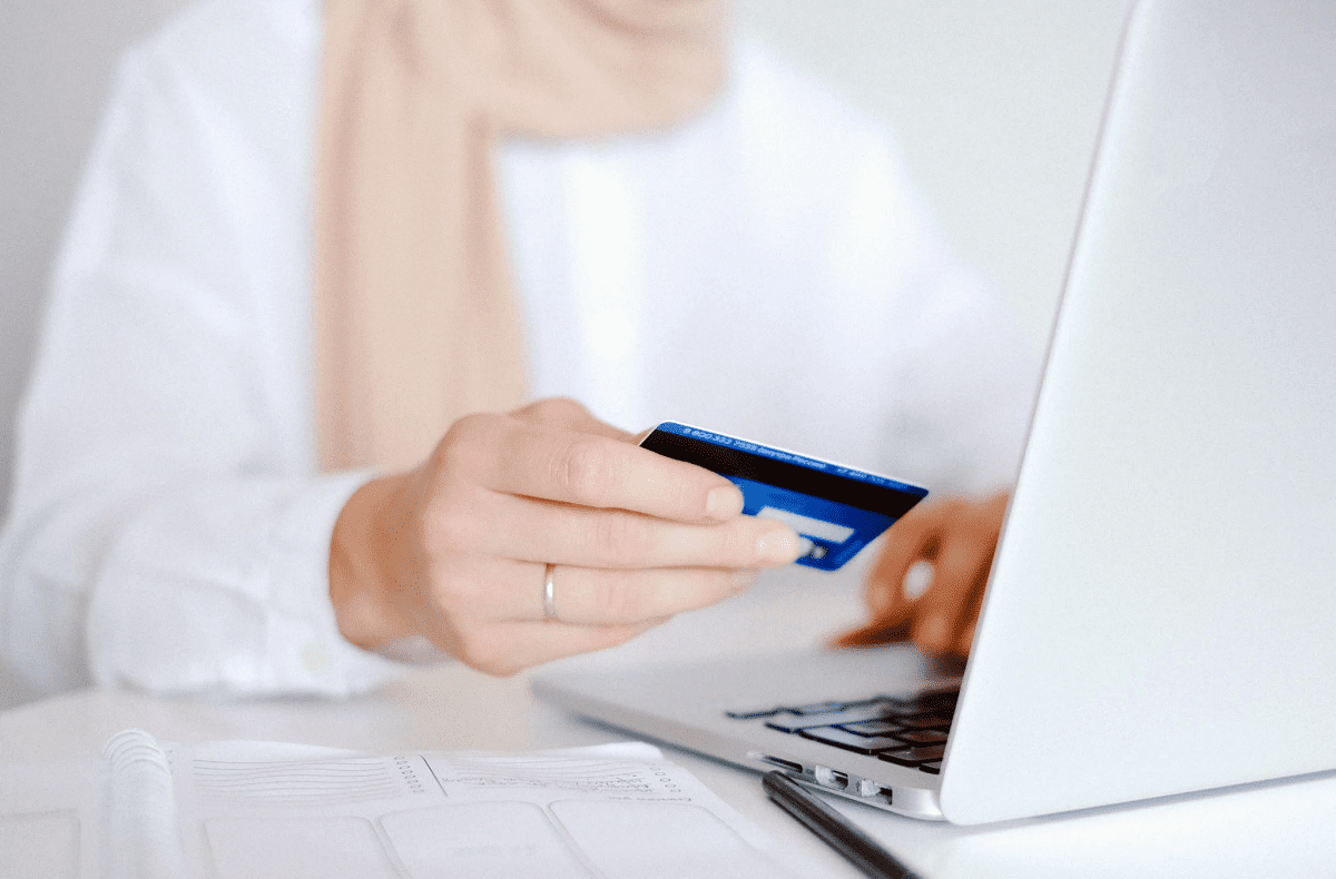 Hands holding credit card, typing on the keyboard of laptop