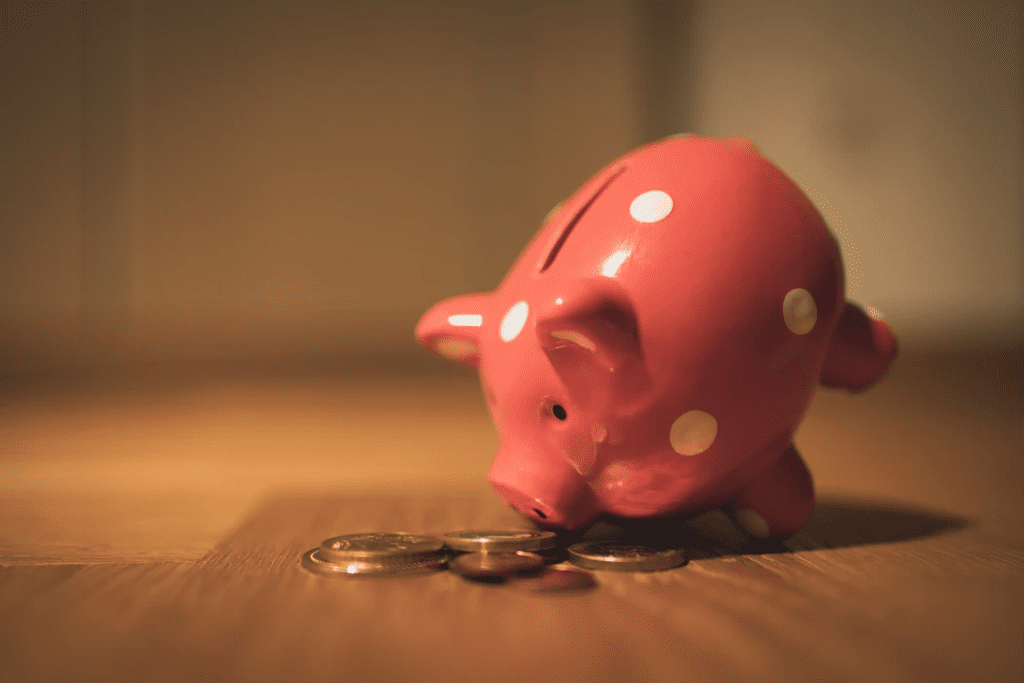 piggy bank with coins on wooden table